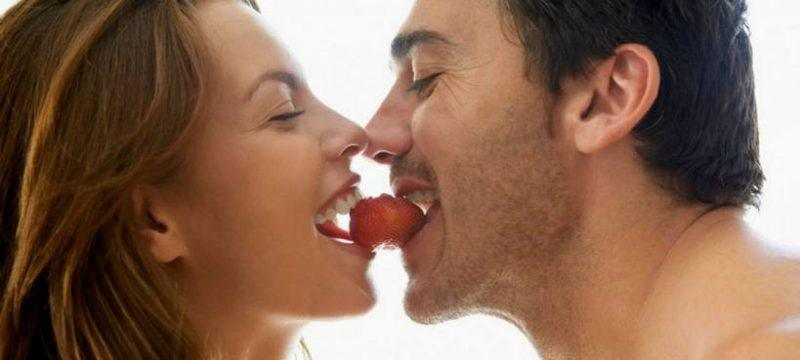 man and woman eating strawberry