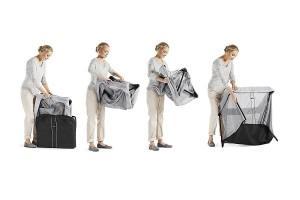 a woman unpacking a Babybjorn playard