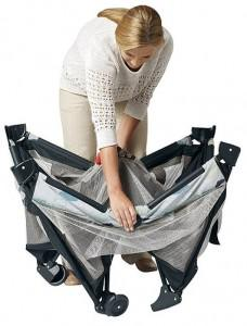 a woman folding the pack and play on the go playard