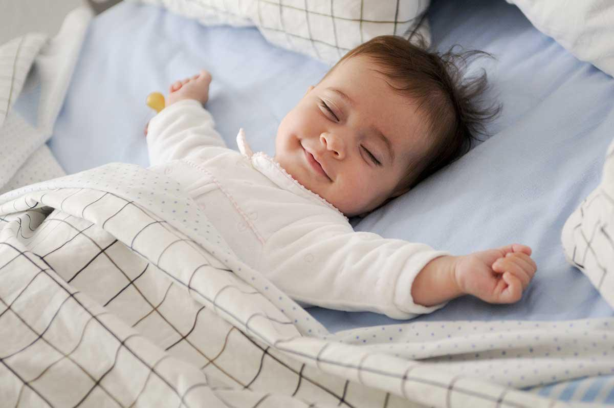 a happy baby sleeping in its bed